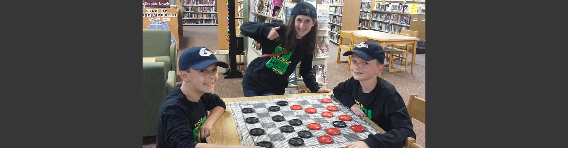 Students playing checkers in library.